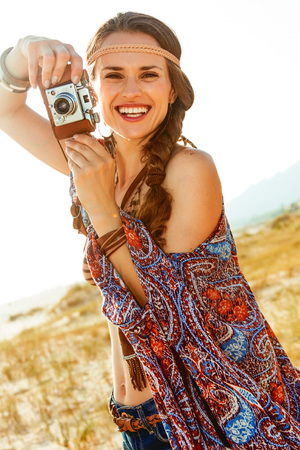 Bohemian vibe vacation. happy stylish boho girl in jeans shorts and cape outdoors in the summer evening holding retro photo camera