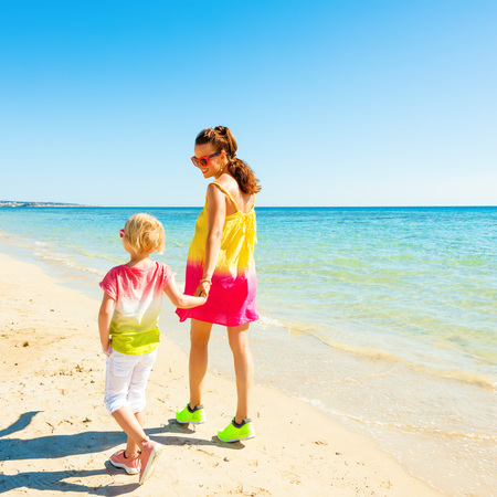 Colorful and wonderfully cheerful mood. Seen from behind modern mother and daughter in colorful clothes on the beach walking Stock Photo