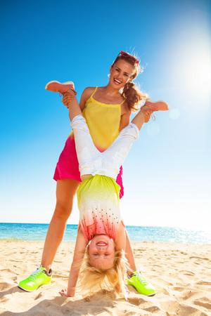 Bunte und wunderschöne fröhliche Stimmung . In voller Länge Portrait der lächelnden jungen Mutter und Tochter in der bunten Kleidung auf der Seeküste mit der Zeit Standard-Bild - 96041344