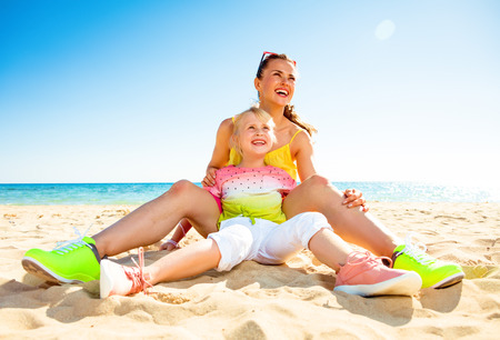 Colorful and wonderfully cheerful mood. happy trendy mother and child in colorful clothes on the beach looking into the distance