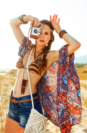 Bohemian vibe vacation. Portrait of trendy hippie in jeans shorts and cape outdoors in the summer evening with retro photo camera