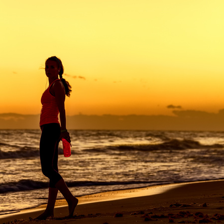 Refreshing wild sea side workout. Silhouette. Full length portrait of healthy woman in sportswear on the beach with bottle of water