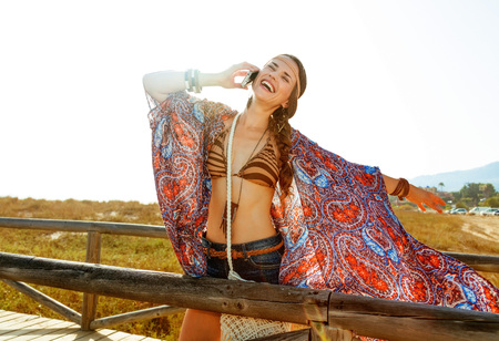 Bohemian vibe vacation. smiling modern boho girl in jeans shorts and cape outdoors in the summer evening rejoicing and using a cell phone Banco de Imagens