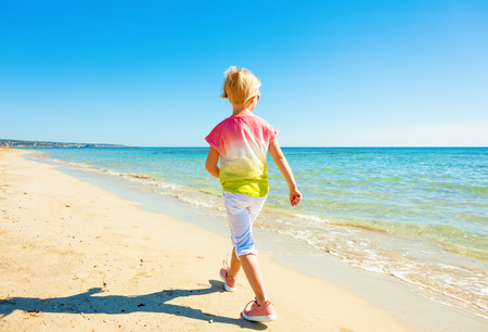 Colorful and wonderfully cheerful mood. Seen from behind modern child in colorful shirt on the seashore walking