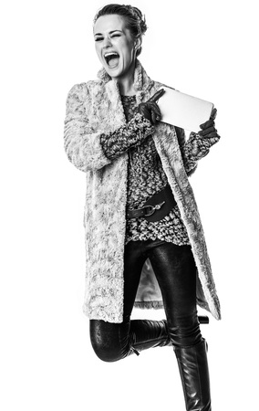 Winter things. happy stylish fashion-monger in winter coat isolated on white with tablet PC