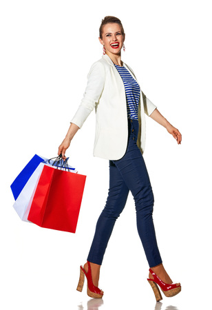 Luxury Shopping. The French way. Full length portrait of smiling young woman in white jacket isolated on white with shopping bags painted in the color of the French flag walking Stock Photo