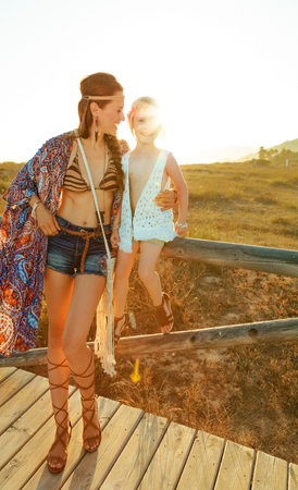 Bohemian vibe vacation. Full length portrait of happy hipster mother and daughter outdoors in the summer evening sitting on a fence Stock Photo