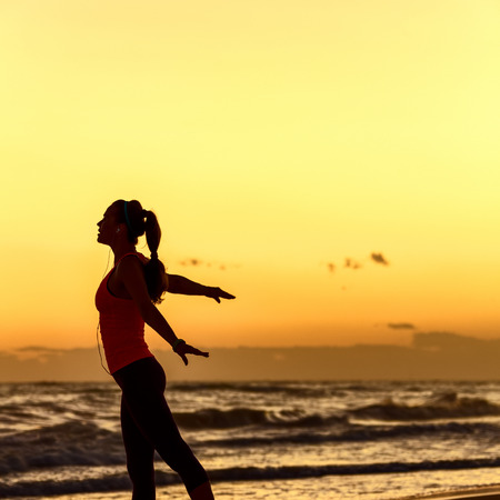 Refreshing wild sea side workout. Silhouette. Full length portrait of active woman in sportswear on the beach rejoicing