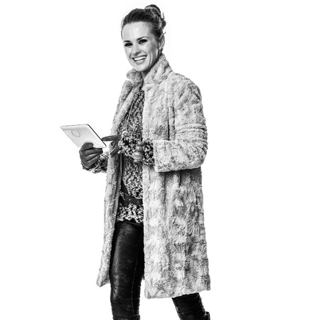 Winter things. Full length portrait of smiling stylish fashion-monger in winter coat isolated on white background using tablet PC Stock Photo
