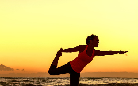 Refreshing wild sea side workout. Silhouette. Full length portrait of active woman in sport clothes on the seacoast stretching Stock Photo