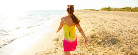 Colorful and wonderfully cheerful mood. Seen from behind trendy woman in colorful dress on the seashore in the evening walking Stock Photo