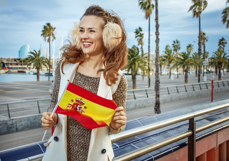 in Barcelona for a perfect winter. smiling trendy woman in earmuffs on embankment in Barcelona, Spain with Spanish flag looking into the distance