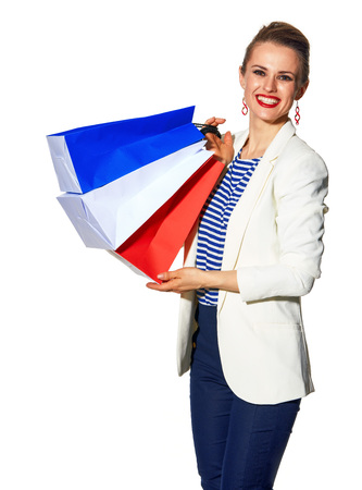 Luxury Shopping. The French way. Portrait of happy trendy fashion-monger in white jacket isolated on white background with shopping bags painted in the color of the French flag Stock Photo