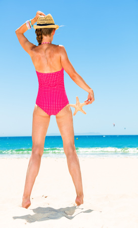 Seen from behind young woman in colorful red swimsuit on the beach with starfish looking into the distance