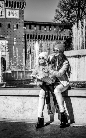 Full length portrait of smiling modern mother and daughter tourists in sunglasses in Milan, Italy holding map and pointing Banque d'images - 95896399