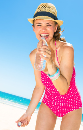 smiling young woman in colorful red beachwear on the beach drinking water from bottle