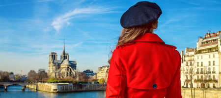 Seen from behind trendy woman in red trench coat on embankment near Notre Dame de Paris in Paris, France