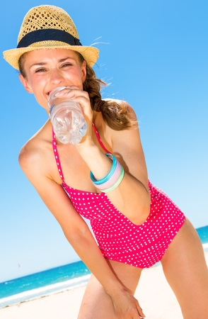 Blue sea, white sand paradise. happy young woman in colorful red swimwear on the seashore drinking water from bottle Imagens