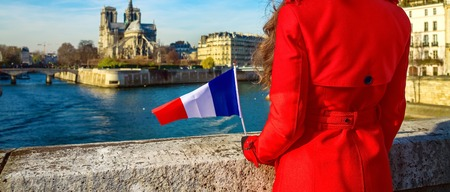 Closeup on modern traveller woman in red trench coat on embankment near Notre Dame de Paris in Paris, France with French flag