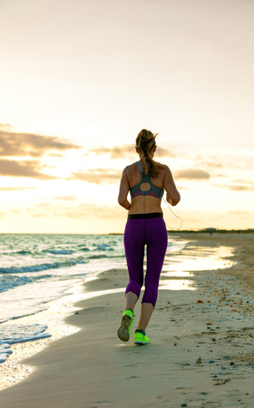 Full length portrait of young woman in sport clothes on the seashore at sunset jogging