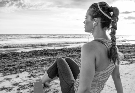 Seen from behind pensive young fit woman in sportswear on the seashore relaxing after workout