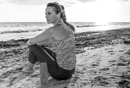 pensive healthy woman in sport clothes sitting on the seashore and looking into the distance