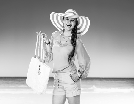 Portrait of happy young woman in shorts and yellow blouse with white beach bag on the seacoast