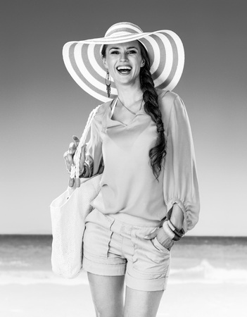 Portrait of smiling active woman in shorts and yellow blouse with white beach bag on the beach