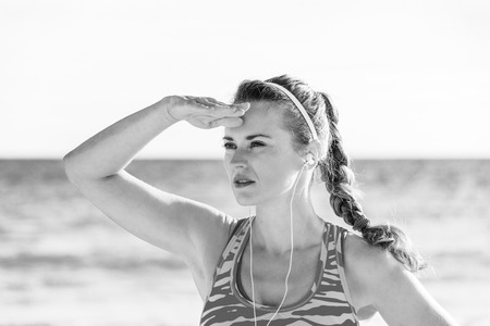 healthy fit woman in sports gear on the seashore looking into the distance and listening to the music with headphones