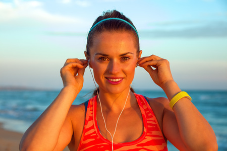 Refreshing wild sea side workout. Portrait of happy active woman in sport clothes on the seashore at sunset with headphones listening to the music Stock Photo
