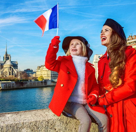 stylish mother and child travellers in red coats on embankment near Notre Dame de Paris in Paris, France rising flag