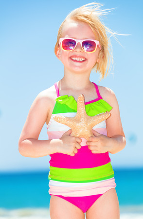 Portrait of happy modern child in colorful beachwear on the seacoast with starfish
