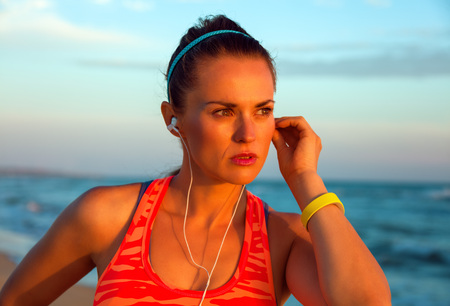 Portrait of young woman in sportswear on the beach at sunset looking into the distance and listening to the music with headphones 版權商用圖片