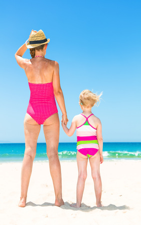 Seen from behind young mother and child in colorful beachwear on the seashore looking into the distance Stock Photo