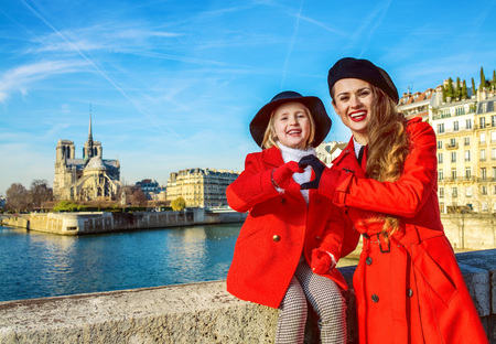 stylish mother and daughter travellers in red coats on embankment in Paris, France showing heart shaped hands Stock Photo