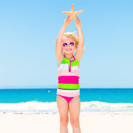 Full length portrait of happy modern child in colorful swimsuit on the seacoast showing starfish Stock Photo