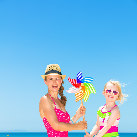Portrait of smiling modern mother and daughter in bright beachwear on the beach holding colorful windmill toy