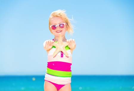 Portrait of happy modern girl in colorful beachwear on the beach showing starfish Stock Photo
