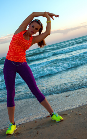 healthy woman in sports gear on the seacoast at sunset stretching