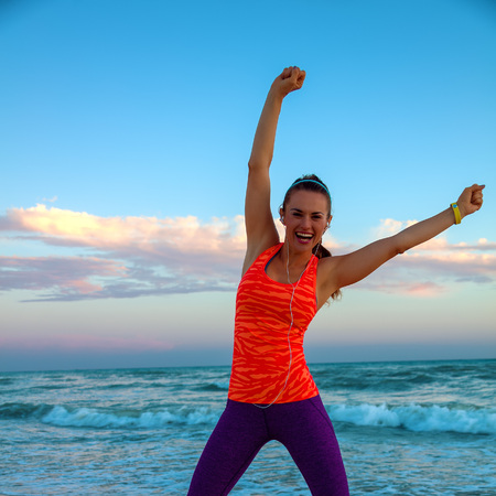 Full length portrait of happy active woman in sportswear on the seashore at sunset rejoicing Stock Photo