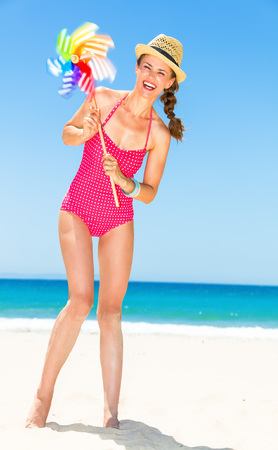 Full length portrait of smiling young woman in bright red swimwear on the beach with colorful windmill toy