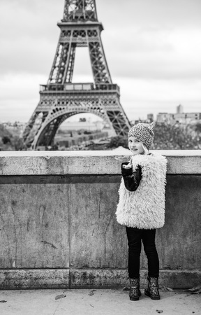 Bold Winter in Paris. Full length portrait of happy trendy child  calling to see Eiffel tower. Paris, France Banque d'images - 100036946