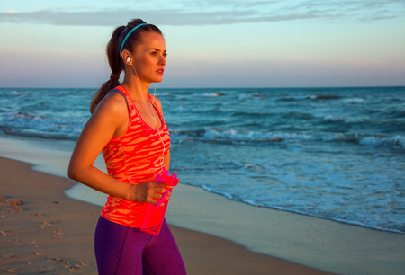 Refreshing wild sea side workout. Portrait of fit woman in sport clothes on the seashore at sunset with bottle of water looking into the distance