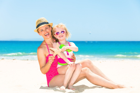 Blue sea, white sand paradise. smiling young mother and child in colorful swimwear on the beach showing starfish Stock Photo