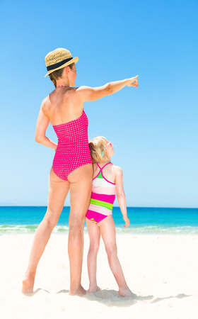 Blue sea, white sand paradise. Seen from behind young mother and child in colorful swimsuit on the beach pointing at something Stock Photo