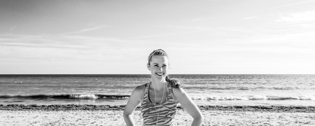 Refreshing wild sea side workout. smiling healthy fitness woman in sports gear on the beach looking into the distance