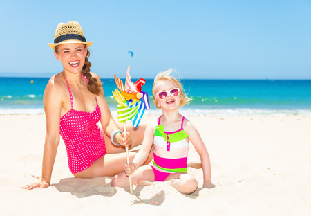 smiling modern mother and daughter in bright beachwear on the seashore with colorful windmill toy Banco de Imagens