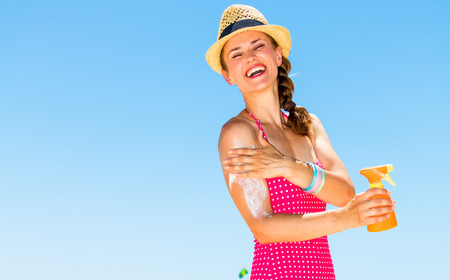Blue sea, white sand paradise. Full length portrait of happy young woman in colorful red swimwear on the seacoast applying SPF