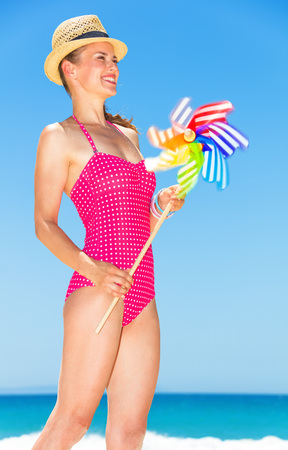 Blue sea, white sand paradise. smiling young woman in bright red swimwear on the seashore with colorful windmill toy looking into the distance Banco de Imagens