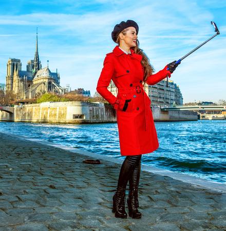 Bright in Paris. smiling elegant tourist woman in red trench coat on embankment near Notre Dame de Paris in Paris, France taking selfie using selfie stick Stock Photo